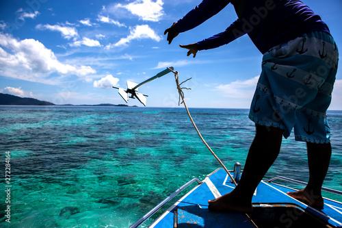 In de dag Schip man drops anchor from the boat in lipe island, Thailand.