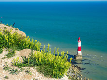 View Of The White Chalk Headland Cliffs And Beachy Head Lighthouse In Seven Sisters National Park, Eastbourne, East Sussex, England, UK.