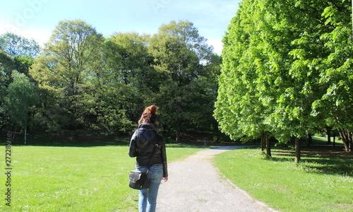 Obraz na plátně  Giovane donna che passeggia da sola nel parco in primavera