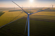 canvas print picture - Aerial view of Eolian generators in a beautiful wheat field. Eolian turbine farm. Wind turbine silhouette. Wind field turbines. Wind propeller. Electric power production. Green energy. Morning light