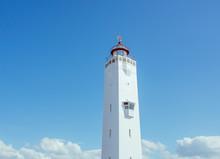 White Lighthouse On Blue Sky Background Near The Sea