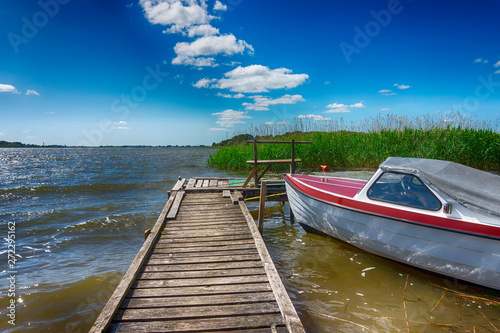 Tuinposter Pier Small motorboat moored alongside a wooden jetty