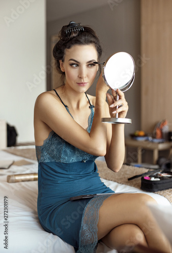 Beautiful woman doing make-up in the bedroom