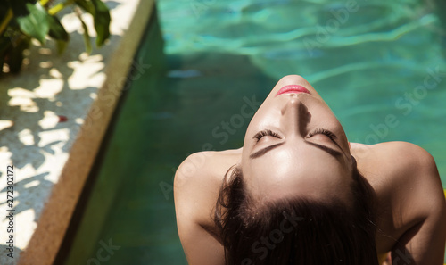 Sensual young lady relaxing by the tropical pool