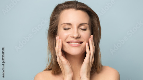 Beautiful smiling young woman with perfect skin touching face Wallpaper Mural