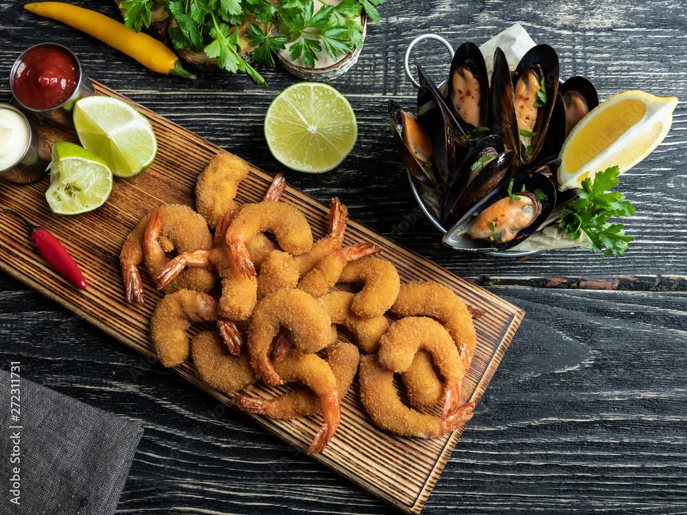 Obraz fried breaded shrimps, mussels served with lime on wooden board, delicious deep, red, white sauce fototapeta, plakat
