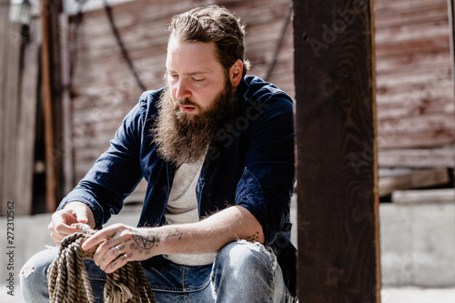 Fotografiet  Brutal man with a beard dressed in casual clothes with tattos on his hands holds