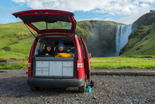 Couple Relaxing In A Red Minivan, Skogafoss Waterfall In The Background, Iceland