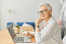 Modern Electronic Gadgets, Occupation, Age And Maturity Concept. Side View Of Attractive Stylish Middle Aged Self Employed Female In Glasses Sitting In Front Of Open Laptop, Working At Home Office