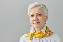 Human Facial Expressions, Feelings, Emotions And Reaction. Close Up Studio Shot Of Beautiful Middle Aged Female Pensioner With Short Gray Hair Frowning Eyebrows, Having Concentrated Serious Look