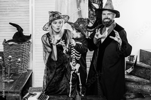 Staande foto Muziekband Halloween scary family. Parents and child in costumes for a party. Skeleton, wizard and witch for halloween home party.