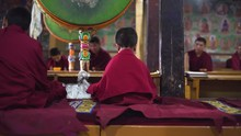 Slow Motion Medium Shot As A Young Buddhist Novice Sitting With His Back On Prayer, Int He Monastery. Selective Focus With Blurred Background