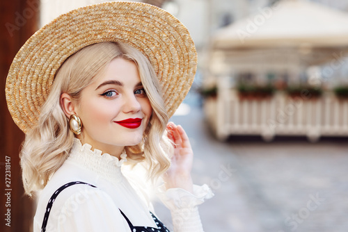 Close up portrait of young beautiful happy lady with red lips makeup, wearing wide brim straw hat, big pearl earrings, posing in street of European city. Copy, empty space for text