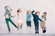 canvas print picture - Girls and boys having fun while jumping against colorful wallpaper. Friends in the school