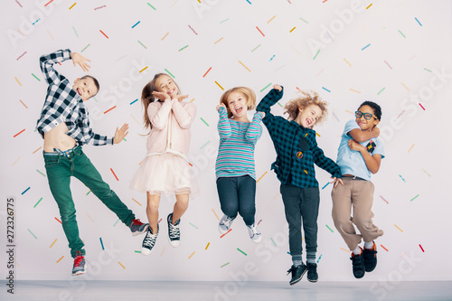 Girls and boys having fun while jumping against colorful wallpaper. Friends in the school - 272326775