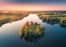 Aerial View Of Beautiful Small Island With Green Trees In The River At Sunset In Summer. Colorful Landscape With Island, Meadow, Forest And Sky Reflection In Blue Water. Top View From Air. Nature