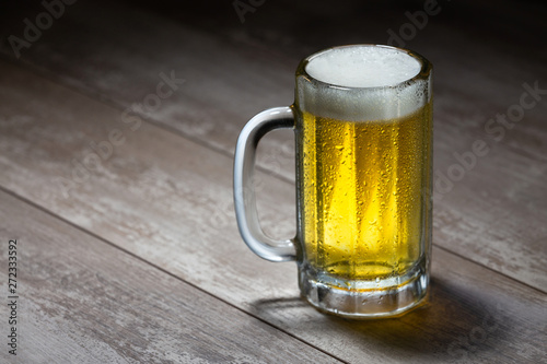 Photo Delicious bright beer stein with frothy foam, poured fresh from the tap, on wood