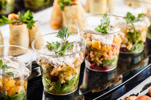 Canvas Print Delicious appetizers with salmon, shrimp, cheese and greens in glass cups on banquet table