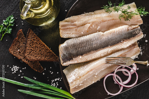 Photo  Marinated fillet mackerel or fillet herring fish with spices, greens and slice of bread on plate over dark stone background