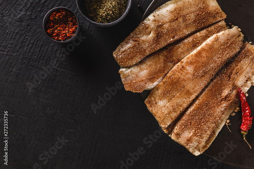 Marinated fillet mackerel or fillet herring fish with spices, greens and slice of bread on plate over dark stone background Canvas Print