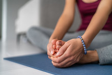 Yoga Leg Stretches Woman At Home. Seated Butterfly Legs Stretch Holding Soles Of Feet Together. Closeup Of Hands Holding Barefoot Feet On Exercise Mat.