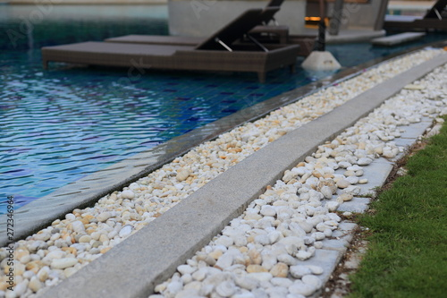 swimming pool grating covered with round white river pebble ...