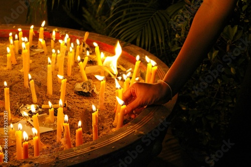 Photo  Many candles illuminate in the dark, filmed as blurred