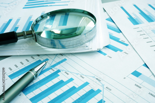 Foto auf Leinwand Texturen Assessment and audit. Business papers with financial charts and Magnifying glass.