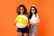 canvas print picture - Happy African American and Asian woman friends with colorful beach ball