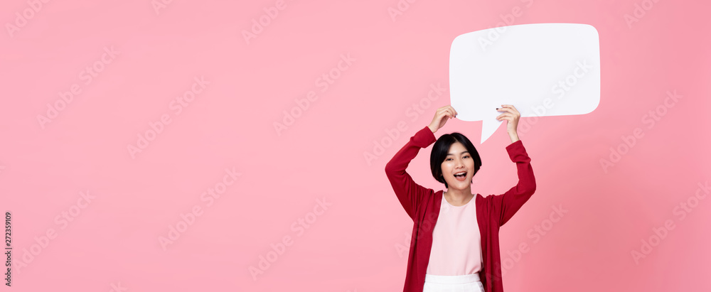Fototapety, obrazy: Smiling young Asian woman holding empty speech bubble in pink background