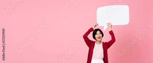 Fotografía  Smiling young Asian woman holding empty speech bubble in pink background