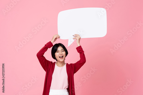 Fotografering  Smiling young Asian woman holding empty speech bubble in pink background