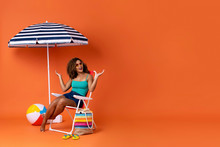 Amazed African American Woman Sitting On A Beach Chair