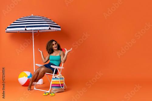 Fotografia Amazed African American woman sitting on a beach chair