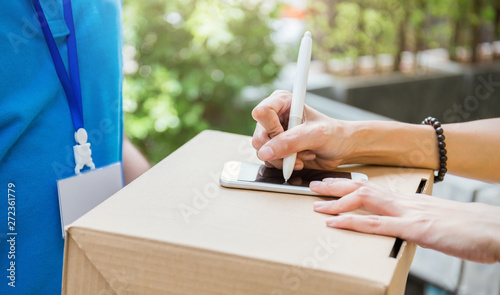 Photo Close up woman hand appending receive sign signature after accepting a delivery of box from delivery man