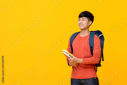 Photo  Asian male college student with backpack holding books