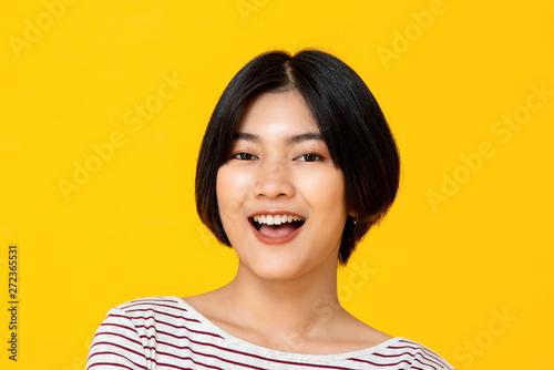 Fotografia  Young beautiful smiling Asian woman in yellow background
