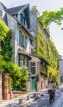 Girl On Bicycle Climbs Up The Cobblestone Pavement Of Old Paris As She Drives Past Green-filled Houses