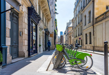 Green Electric Bicycles With Baskets For Public Rent Stand In Row On Street Of Paris Awaiting Cyclists