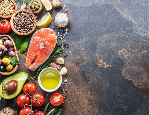 Valokuva  Raw salmon with spices and vegetables on the graphite board.