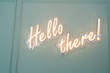 Neon Glowing Sign With Word Hello There And Green Wall