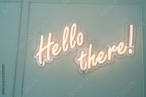Fototapeta Neon glowing sign with word Hello there and green wall
