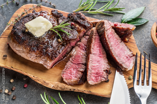 Papiers peints Steakhouse Medium rare Ribeye steak with herbs and a piece of butter on the wooden tray.