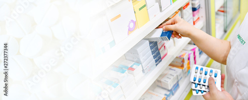 Fotobehang Apotheek Pharmacist holding medicine box and capsule pack in pharmacy store and white pill background for copy space