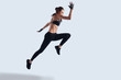 Real freedom. Full length of attractive young woman in sports clothing exercising while hovering against grey background
