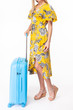 girl in a yellow dress. blue luggage. girl travels with suitcases. White background