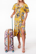 girl in a yellow dress. big luggage. girl travels with suitcases. White background