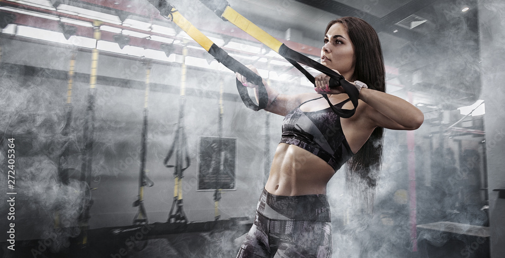 Fototapety, obrazy: Sport backgrounds. Powerful attractive muscular woman fitness trainer do battle workout with ropes at the gym.