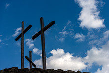 Three Christian Crosses Above A Hill With Blue Sky And Clouds. Religious Symbol Of Good Friday