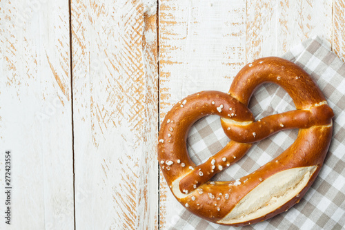 Traditional German savory lye pretzel with salt on checkered cotton kitchen towel on white plank wood table Wallpaper Mural
